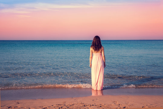 Young woman in a long dress back to camera at sunset on the beach
