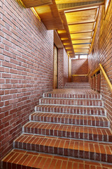 Red brick walls and staircase with wooden roof interior corridor