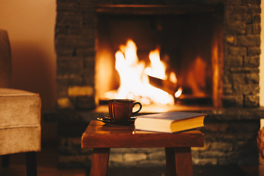 Cup of hot tea with a book in front of warm fireplace