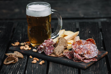 Photo sur Aluminium Buffet, Bar Mug of beer and snacks on wooden board on dark wood background. Kielbasa, cheese, nuts, toasts