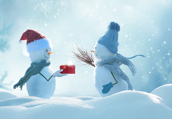 Wall Mural - Merry christmas and happy new year greeting card .Two cheerful snowmen  standing in winter christmas landscape.