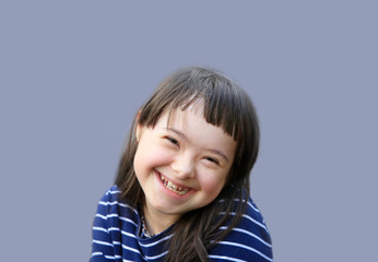 Cute smiling down syndrome girl on the blue background