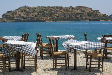 Tables and chair of the street restaurant in Greece in the windy day