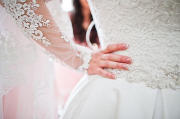 Close-up photo of bride's hand on her waist, holding wedding dress.