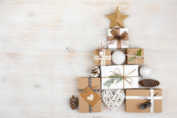 Christmas gifts in shape of fir tree on wooden background