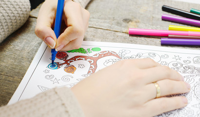 An image of a new trendy thing called adults coloring book. In this image a person is coloring an illustrative and detailed pattern for stress relieve for adults.
