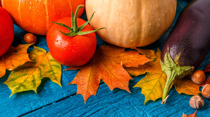 Image of blue wooden table with autumn leaves, pumpkin