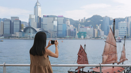 Woman taking photo with cellphone in Hong Kong Victoria harbor