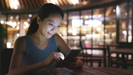 Woman uses mobile phone in outdoor cafe