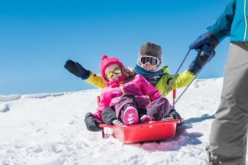 Father playing with children on snow