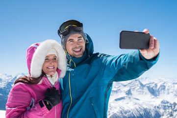 Couple taking selfie in snowy mountain
