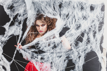 Halloween witch girl cought in spider network in a blouse and red skirt.