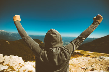 Achievement and triumph. Victorious female person on mountain top. Fotobehang