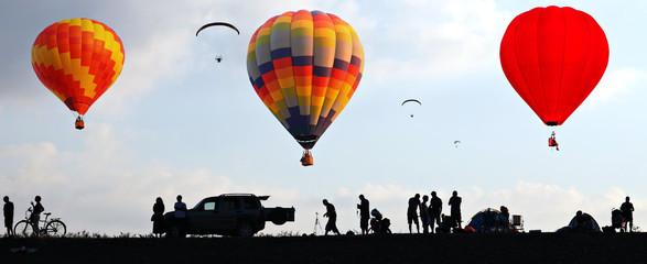 Hot air colorful balloons flying in the sky  Silhouettes of people watching the flight from the ground. Panorama