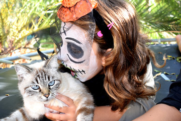 Little witch with a cat on Halloween Party