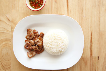 fried pork with garlic and rice on wood background , Thai food