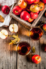 Fresh organic farm apple juice in glasses with raw whole and sliced red apples, on old rustic wooden table, copy space top view
