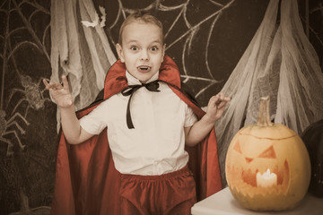 Portrait of funny cute little boy posing for photography in costume of vampire in beautiful Halloween decor in black and white colors. Filtered in vintage style horizontal color photo.