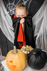 Portrait of funny cute little boy hiding face in costume of vampire. Baby playing in beautiful Halloween decor in black and white colors. Vertical color photo.
