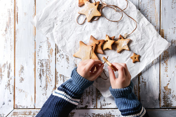 Child hands make garland of homemade shortbread star shape sugar cookies different size on thread on baking paper over white wooden plank table. Christmas handmade gift. Top view with space