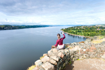 Woman traveller sitting on mountain top making picture by smartphone