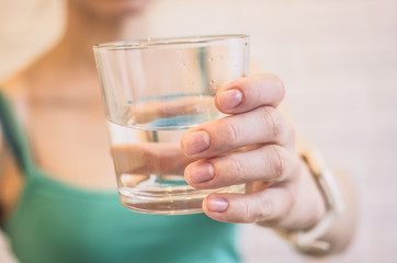 Glass with pure water in a female hand close-up