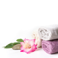 Spa setting of towel, flower isolated on white background with copy space.