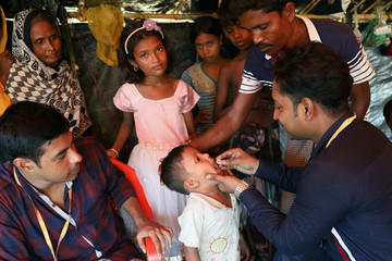 A healthcare member administers oral cholera vaccine distributed by WHO to a Rohingya refugee child in the Jamtoli refugee camp in Cox's Bazar