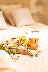 Continental breakfast on bed in elegant bedroom interior
