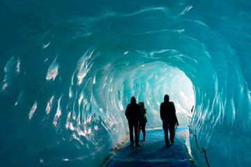 Silhouettes of people visiting thee ice cave of the Mer de Glace glacier,  in Chamonix Mont Blanc Massif, The Alps, France