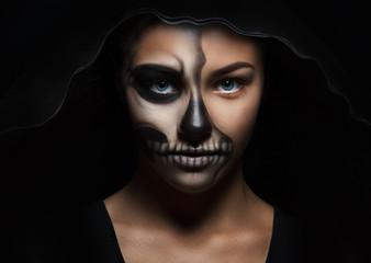 Halloween portrait of young beautiful girl in a black hood. skeleton makeup half face