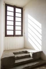Dettaglio dei raggi solari che attraversano una delle finestre dell' antico palazzo Farnese a Caprarola, vicino Roma, in Italia. Gli infissi sono in legno e il muro bianco..
