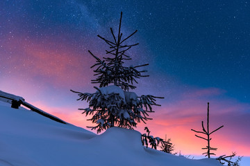 Colorful winter alpine landscape at night with starry sky and glow of sunset