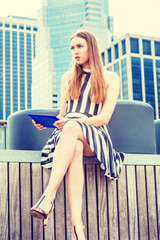 Young Beautiful European Woman traveling, reading blue tablet computer, relaxing at street park in New York in summer, wearing black, white striped short dress, sandals, sitting on wooden stairs..