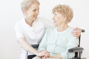 Smiling caregiver hugging senior woman