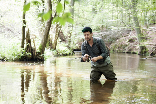 A patient man in waders is fly fishing on a river in forest area.