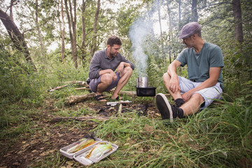 Two men are preparing the grill for a barbeque in open nature.