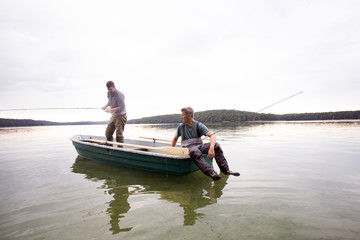 Two men in waders are fly fishing from a boat in a lake.