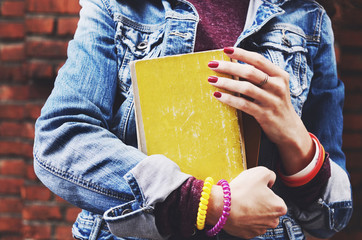 Young student in jeans jacket holding books in her hands