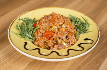 A plate of rice with vegetables. Appetizing healthy rice with vegetables in white plate on a wooden background.