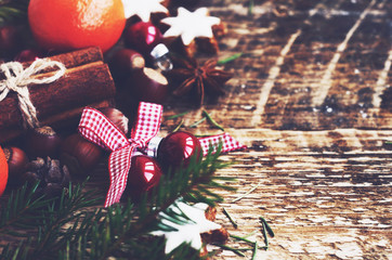 Winter decoration with festive balls with ribbon and bow and xmas fir tree with copy space on wooden background
