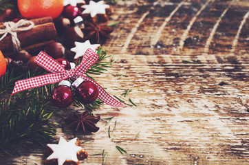 Christmas background with gingerbread cookie stars, fir tree twigs, red balls, spices and fresh tangerines on wooden boards