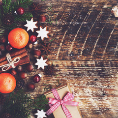 Xmas decoration with gift box, cinnamon, gingerbread cookies, fresh clementines, fir twigs and nuts with copy space on wooden background