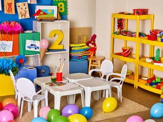 School interior with paint and crayon. No people in kindergarten or preschool. Classroom Interior with chairs, table and toys.