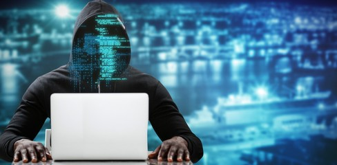 Composite image of male hacker using laptop on table