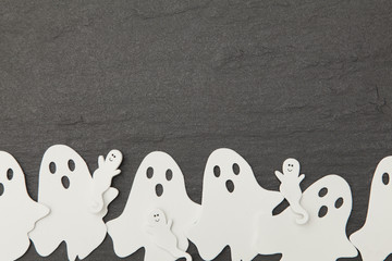 Halloween ghost shapes on a slate background