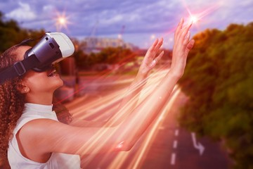 Composite image of young woman looking through virtual reality