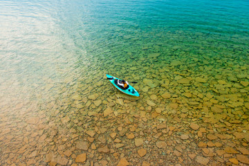 Woman in Sea Kayak Paddling on Crystal Clear Freshwater Lake at Summer Family Cottage