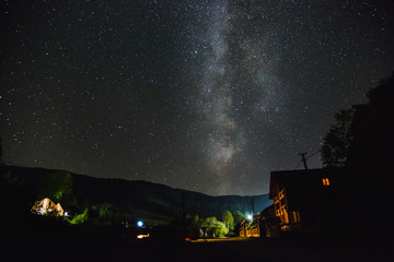 The Milky Way over the mountains and the village on a summer night.