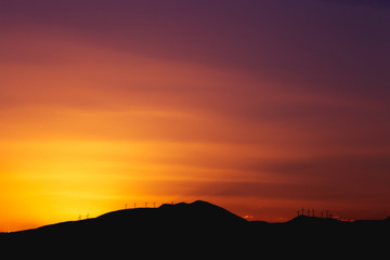 Mountain Ridge with Windmills over a Dark Red Sunset